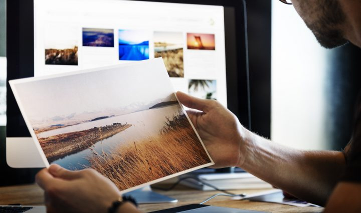 The man working with photo editing software and holding a photo print