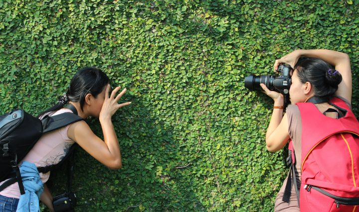 Two girls taking shots with DSLR for a beginner against the green hedge